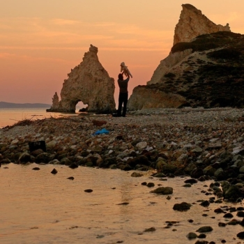 Greece, Cyclades. Kimolos. Faily affection in Mavrospilea beach. Sunset between the white rocks.