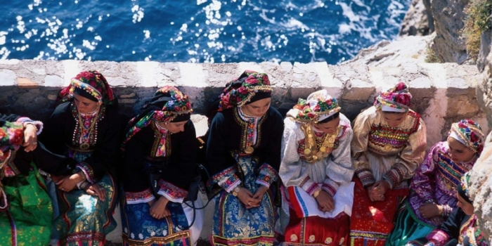 Karpathos, Olymbos: Untouched by Time Vroukounda, young girls in traditional  costumes sit on a stone parapet